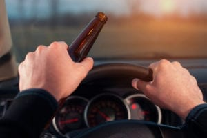 Driving under alcohol influence. Drunk driver with beer bottle in car.