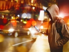Hacker anonymous using smartphone on the street at night