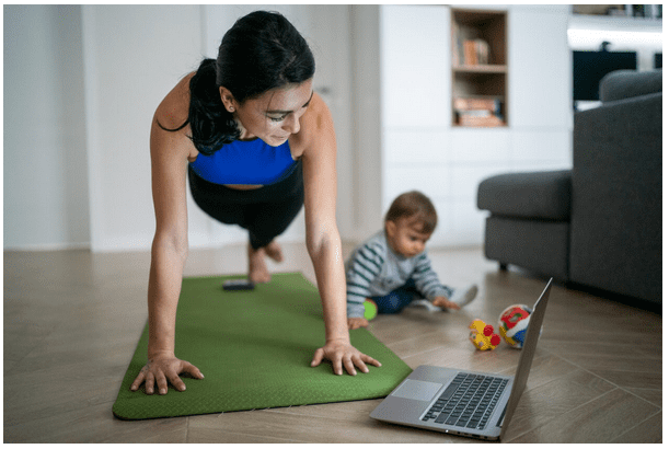 Woman Exercising while looking at a Laptop